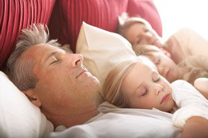 Image of Family of Four Sleeping Soundly on Comfortable Mattress.